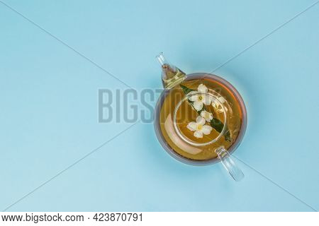 Top View Of A Glass Teapot With Jasmine Tea On A Blue Background. An Invigorating Drink That Is Good