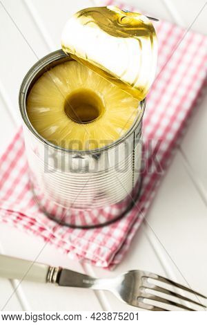 Canned sliced pineapple fruit in can on white table.