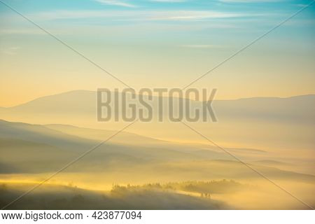 Mountainous Countryside Landscape At Foggy Sunrise. Wonderful Autumnal Nature Scenery With Distant R