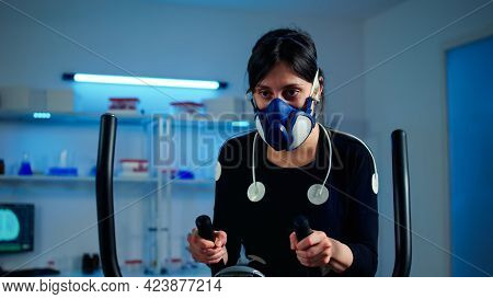 Tired Athlete Woman Training On Cross Trainer Increasing Rhythm Of Exercises Wearing Mask And Medica