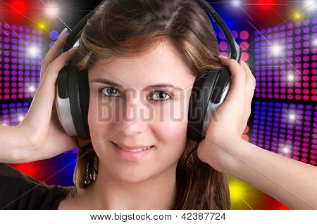 Young woman listening to music through her headphones isolated in a whiite background poster