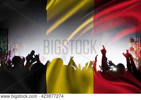 Soccer fans supporting Belgium - crowd celebrating in stadium with raised hands against Belgian flag