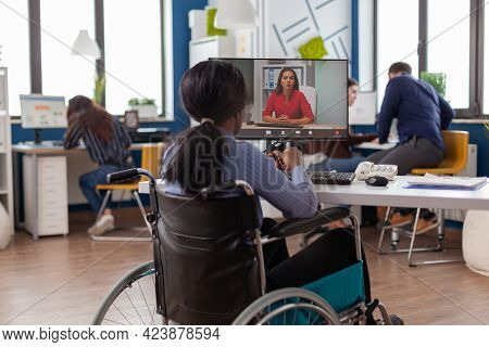 African Disabled Handicapped Businesswoman Sitting Immobilized In Wheelchair Talking With Remote Par
