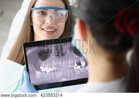 Dentist Doctor Examines X-ray Picture On Tablet Screen In Chair Is Woman Patient