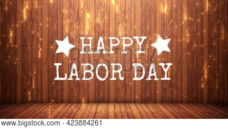 Happy labor day text against golden spots of light on wooden background. american labor day template background design concept