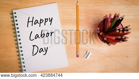Happy labor day text on dairy and pencil stand on wooden surface. american labor day template background design concept