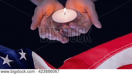 Composition of adult hands holding lit tea light candle above american flag on black. patriotism, independence and celebration concept digitally generated image.