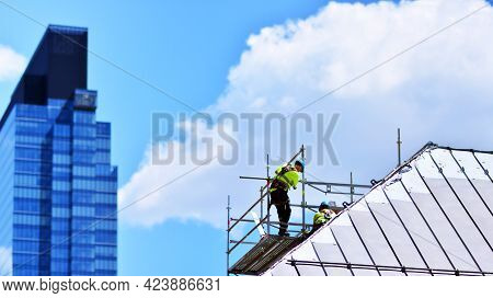 Construction Workers On A Scaffold. In City