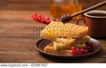 Drops Of Honey Dripping On The Belgian Waffles. Belgian Waffles With Berries And Honey On The Wooden