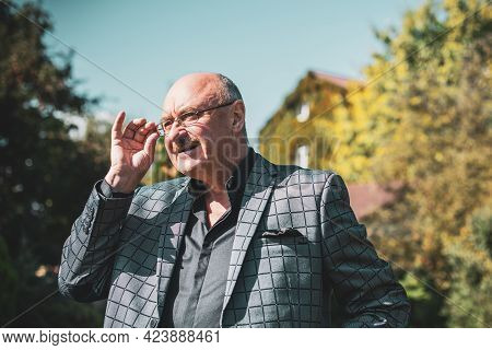 Mature European Or American Man With A Good Mood, Outdoor Portrait. The Concept Of Life After 50-60