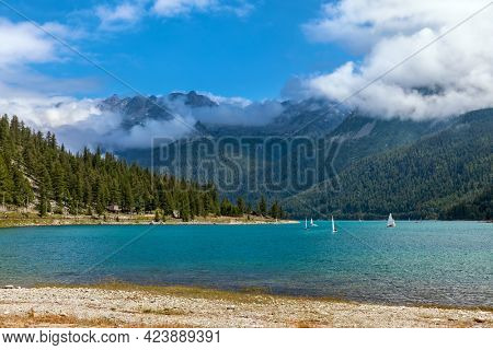 View of beautiful water on Lago di Ceresole and green trees on the mountain's slopes under blew sky with white clouds in Piedmont, Northern Italy.