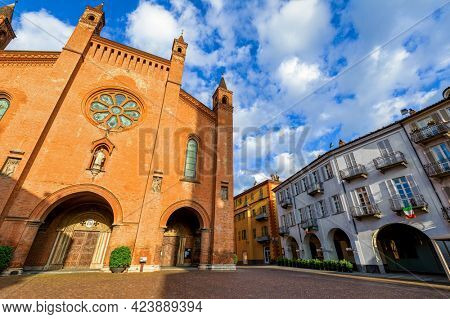 San Lorenzo Cathedral and old houses on cobblestone town square under beautiful sky in Alba, Piedmont, Northern Italy.