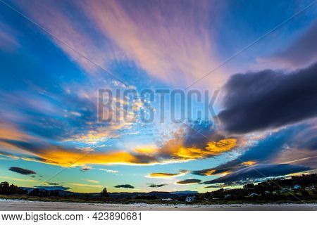 Sunset over the ocean. Gentle fancy clouds colors are reflected in the ocean water. The art of artistic photography. New Zealand, Pacific Coast. The concept of ecological and photo tourism