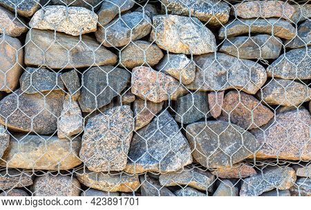Stone Wall With Metal Grid As Background. Rock Texture In Metal Grid. Gabion Net