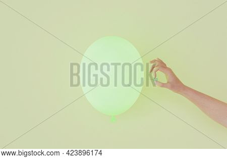 Green Balloon With A Hand Going To Poke It With A Thumbtack. 3d Render