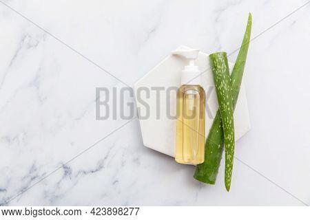 Overhead Shot Of Aloe Vera Cosmetic Bottle And Natural Green Aloe Vera Leaves