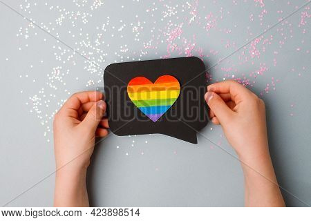 Close Up Of A Person's Hands Holding A Black Social Media Bubble With Heart With The Colored Stripes