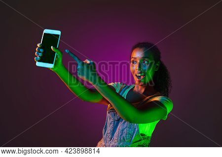 Latino Young Woman With Phone Isolated On Studio Background In Neon. Concept Of Human Emotions, Faci