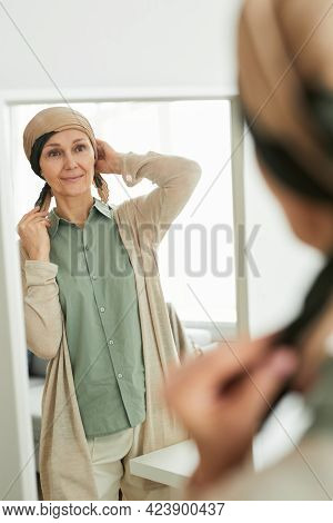 Vertical Portrait Of Mature Woman Putting On Headscarf While Looking At Mirror And Getting Ready To
