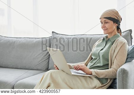 Candid Portrait Of Mature Woman Using Headscarf And Using Laptop While Relaxing On Couch In Cozy Hom