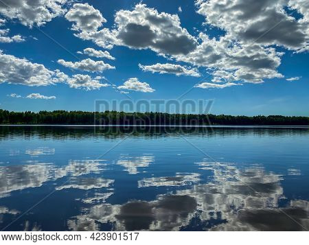 Beautiful Summer Landscape With White Cumulus Clouds Reflected In The Calm Blue Lake Water.