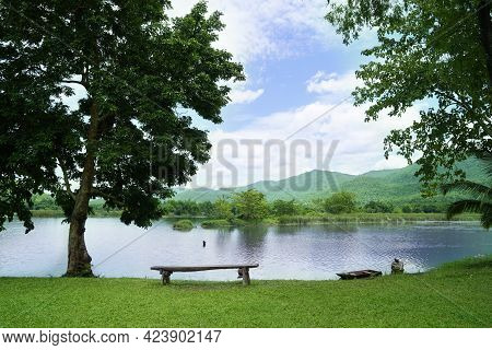 Wooden Chairs Are Placed By The River For Outdoor View With Blue Sky Over The Mountain And Lake View