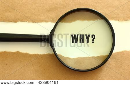 The Magnifying Glass Reveals The Why Text Appearing Behind The Torn Brown Paper. Business Concept