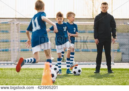 Coaching Kids Soccer. Young Man As Soccer Coach Trainer On Football Children Camp. Soccer Boys In Bl