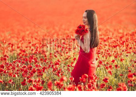 Young Brunette Woman 25-30 Years Old With Long Groomed Hair In Red Dress Enjoy A Poppy Flowers In Fi