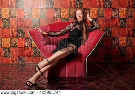 Beautiful young woman in black evening dress sits on the armchair in luxury apartments. Glamorous lifestyle. Beauty, fashion. Modern interior, furniture.