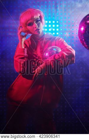 Attractive girl with bright glitter make-up and pink hair poses with disco ball and headphones in neon light. Disco girl. Night party. DJ girl.