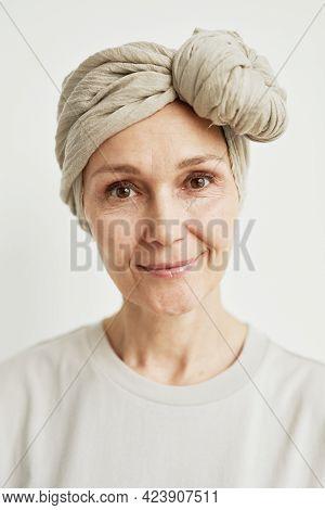 Minimal Close Up Portrait Of Beautiful Mature Woman Wearing Headscarf And Smiling At Camera