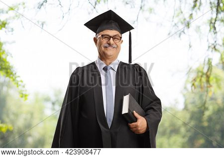 Mature man in a graduation gown holding a book outdoors