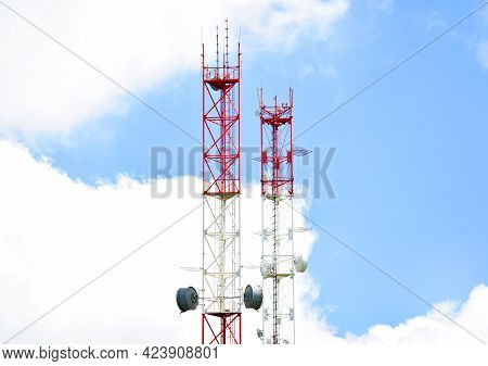 Two Telecommunication Towers With Radio Modules And Antennas Against A Background Of Blue Sky And Cl