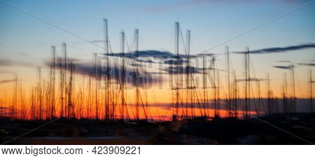 Atmospheric Photo Of Moving Ship Masts In Marina In The Evening With Sunset (deliberately Blurred)