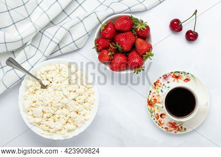 Quark, A Cup Of Black Coffee And Strawberry On A White Table. Hot Morning Drink. Russian Tvorog And