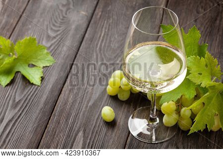 White wine glass and grape on old wooden table
