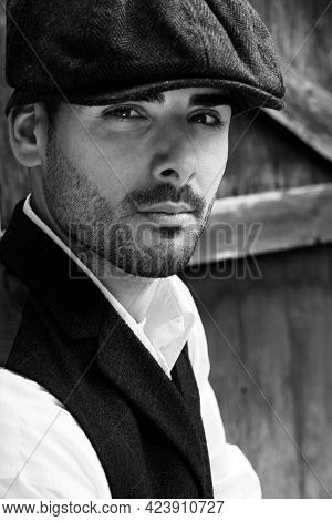 Handsome Latino Gangster Dressed In Waistcoat Sitting And Looking At Camera, Leaning On Gate