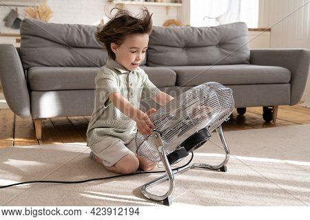 Happy Little Boy Of 5 Refreshing With Big Fan Sitting On Floor In Living Room Alone. Small Preschool