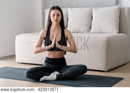 Calm And Peaceful Young Woman Practicing Yoga At Home, Sitting In Lotus Position And Doing Namaste G