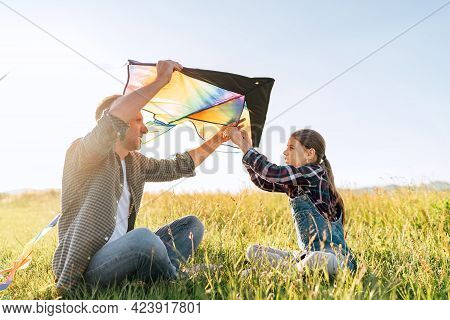 Smiling Girl Sitting On The Grass With Father Helping Her To Prepare Colorful Rainbow Kite Toy For F