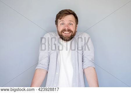 Funny, Smiling Man Innocently Shrugs Shoulders And Looks At The Camera. Gray Background.