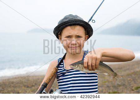 Boy holding a fish (Far eastern dace) caught at sea.