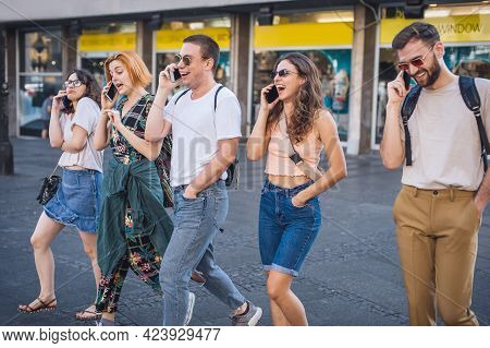 Group Of Friends Walking And Talking In The City Center