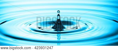 Blue Water drop splash Drop of water drop to the surface. Waves on the surface of the water from a collision