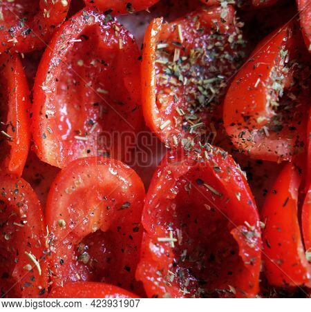 Tomatoes lie on a baking sheet, ready to bake. Sun-dried tomatoes. Close up.