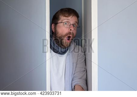 Bearded Man In Casual Clothes Is Hiding In A Closet, He Peeps Through The Open Door And Looks In Sur