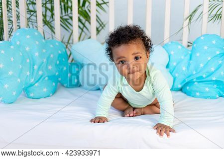 Cute African Baby Sitting In Bed At Home Before Going To Bed On The Blue Bed, The Concept Of Healthy
