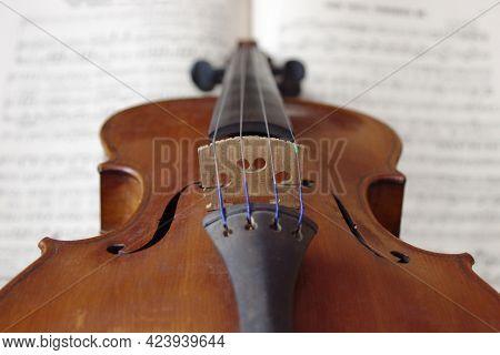 Vintage Brown Violin Music Instrument On White Sheet Music Close Up