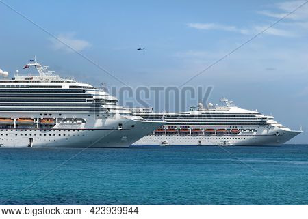 Two View Of A Helicopter Flying Over Two Large Cruise Liners Drifting Near Grand Cayman Island (caym